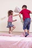 Niños divertidos que juegan con las almohadas en dormitorio Batalla improvisada de los niños Imagenes de archivo