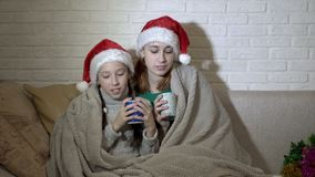 Niños, dos muchachas, cubiertas con una manta, sentada del canto en los sombreros de Papá Noel en el sofá contra una pared blanca almacen de metraje de vídeo