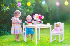 Niños dulces en la fiesta del té de la muñeca Foto de archivo
