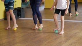 Niños e instructor Exercising con la bola de la tensión almacen de metraje de vídeo