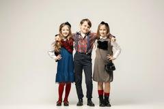 Niños elegantes lindos en el fondo blanco del estudio Imagen de archivo