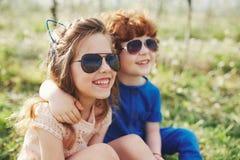 Niños elegantes lindos en parque del verano Imagenes de archivo