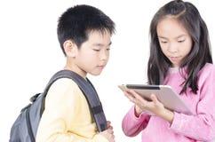 Niños elegantes que usan el ordenador de la almohadilla táctil Fotos de archivo libres de regalías