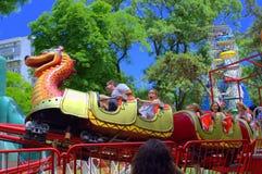 Niños emocionados en el tren del dragón Fotos de archivo