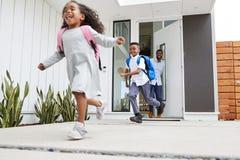 Niños emocionados que corren fuera de la escuela de Front Door On Way To mirada por el padre imagenes de archivo