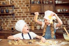 Niños emocionados que juegan con la pasta para las galletas formadas foto de archivo