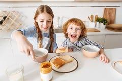 Niños enérgicos agradables que disfrutan de su comida de la mañana Fotos de archivo libres de regalías