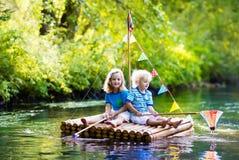 Niños en balsa de madera fotografía de archivo