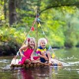 Niños en balsa de madera fotos de archivo