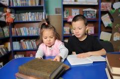 Niños en biblioteca que leen el libro interesante Aprendizaje de la niña y del muchacho fotos de archivo libres de regalías