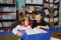 Niños en biblioteca que leen el libro interesante Aprendizaje de la niña y del muchacho imágenes de archivo libres de regalías