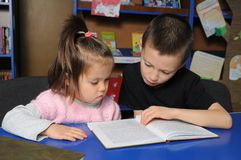 Niños en biblioteca que leen el libro interesante Aprendizaje de la niña y del muchacho foto de archivo libre de regalías