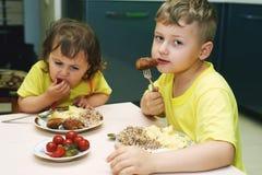 Niños en casa que comen la comida hecha en casa Fotografía de archivo