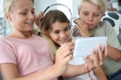 Niños en casa que juegan con smartphone Foto de archivo