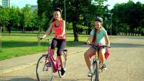 Niños en casco en la bicicleta por cycleway en parque del verano metrajes