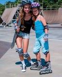 Niños en casco que andan en monopatín en su monopatín Fotos de archivo libres de regalías