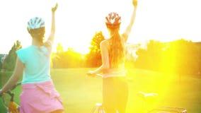 Niños en casco en saludo del sol naciente de la bicicleta en parque del verano almacen de video