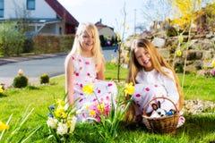 Niños en caza del huevo de Pascua con el conejito foto de archivo libre de regalías