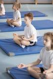 Niños en clase relajante de la meditación foto de archivo libre de regalías