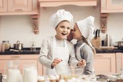 Niños en cocina La hermana está diciendo a hermano un secreto mientras que cocina imagenes de archivo