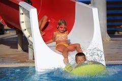 Niños en diapositiva de agua en el aquapark Imágenes de archivo libres de regalías