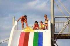 Niños en diapositiva de agua en el aquapark Fotos de archivo libres de regalías