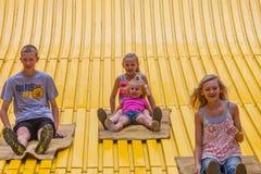 Niños en diapositiva del carnaval en el estado justo Foto de archivo