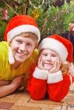Niños en el árbol de navidad del fondo fotos de archivo