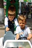 Niños en el área de juego que monta un coche del juguete Nikolaev, Ucrania Foto de archivo