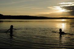Niños en el agua de un lago en la puesta del sol Fotos de archivo libres de regalías