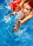 Niños en el colchón inflable rojo en piscina Imagen de archivo libre de regalías