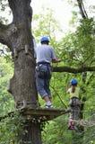 Niños en el curso de las cuerdas en los árboles Imagen de archivo