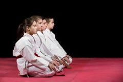 Niños en el kimono que se sienta en tatami en seminario de los artes marciales Foco selectivo imágenes de archivo libres de regalías