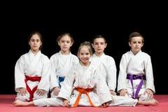 Niños en el kimono que se sienta en tatami en seminario de los artes marciales Foco selectivo imagenes de archivo