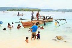 Niños en el mar y peregrinos que vienen a Mansinam Foto de archivo