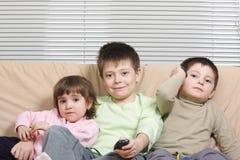Niños en el sofá imagenes de archivo