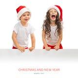 Niños en el sombrero de Papá Noel que salta de detrás la cartelera en blanco de la muestra Foto de archivo