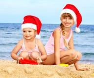 Niños en el sombrero de santa en la playa. Fotos de archivo