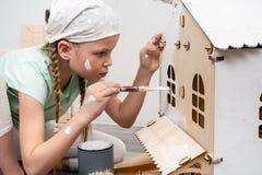 Niños en el trabajo: La muchacha pinta cuidadosamente la fachada de la casa de muñecas con una pequeña borla en blanco imágenes de archivo libres de regalías