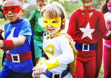 Niños en el traje del super héroe que juega junto Imagenes de archivo