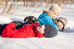 Niños en el winterwear que juega en nieve acumulada por la ventisca Imagen de archivo