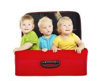 Niños en estuche de viaje, tres viajeros de los niños dentro de la maleta Imagenes de archivo