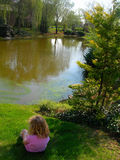 Niños en hierba por el lago Imagenes de archivo