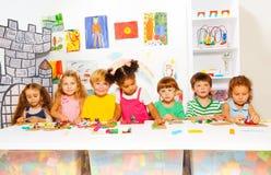 Niños en juego de la clase que se convierte con plasticine Imagen de archivo libre de regalías