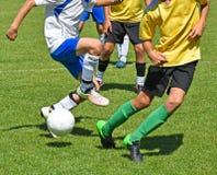 Niños en la acción en el partido de fútbol Imagen de archivo libre de regalías