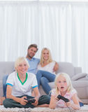 Niños en la alfombra que juega a los videojuegos mientras que sus padres a Imágenes de archivo libres de regalías