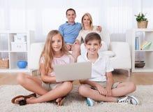 Niños en la alfombra usando la tablilla y la computadora portátil Foto de archivo