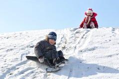 Niños en la colina del invierno. Imagen de archivo libre de regalías