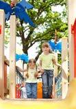 Niños en la diapositiva al aire libre en parque. Imágenes de archivo libres de regalías