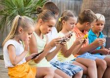 Niños en la edad de escuela que mira los teléfonos móviles y que sienta el outd foto de archivo libre de regalías